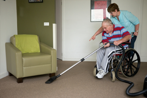 Woman helping a disabled man vacuum